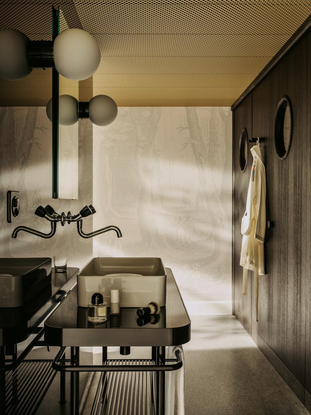 Detailverliebter Waschbereich: Das Lavabo hat eine Insel, in die Toilette und die Dusche blickt  man durch ein rundes Fenster. Kosmetikprodukte von  Soeder stehen zur Benutzung bereit.