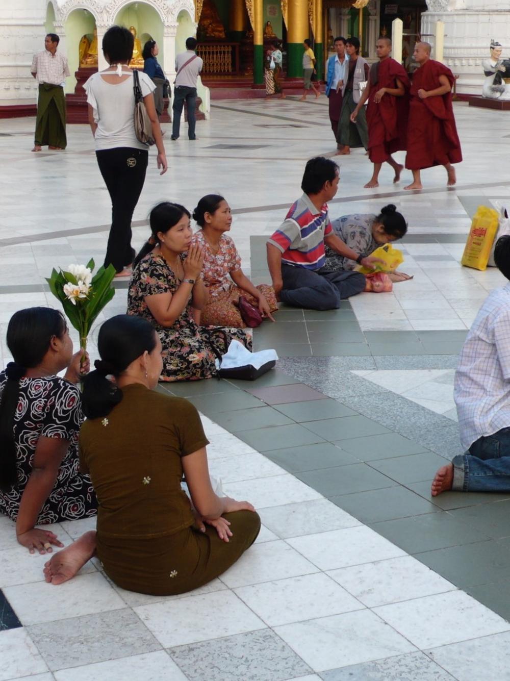 Buddhistische Mönche und Gläubige in einem Tempel, Thailand