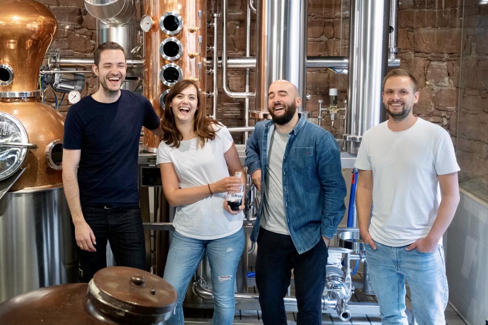 Die Harmonie scheint zu stimmen: Chris, Nadia, Pan und Manuel von GRYFF Spirits. Sie posieren in der Stadtbrennerei, wo ihr Gin seine Geschmacksnoten ausbildet.