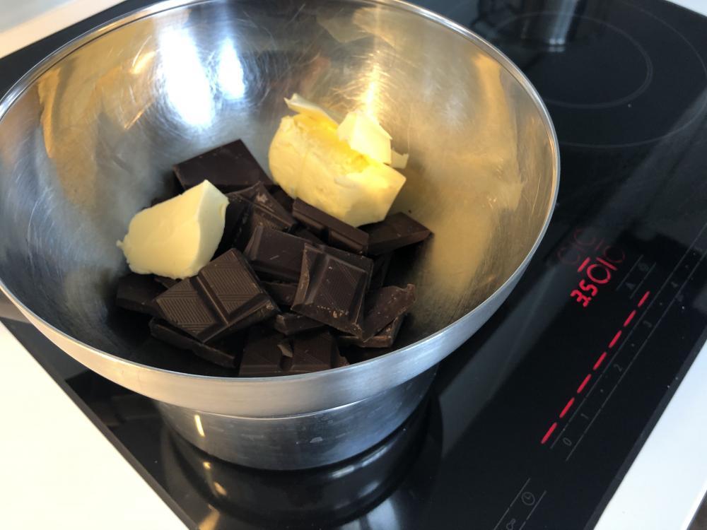 Die Schoggi zusammen mit der Butter im Wasserbad schmelzen. Geht auch direkt in der Pfanne - sogar einiges schneller.