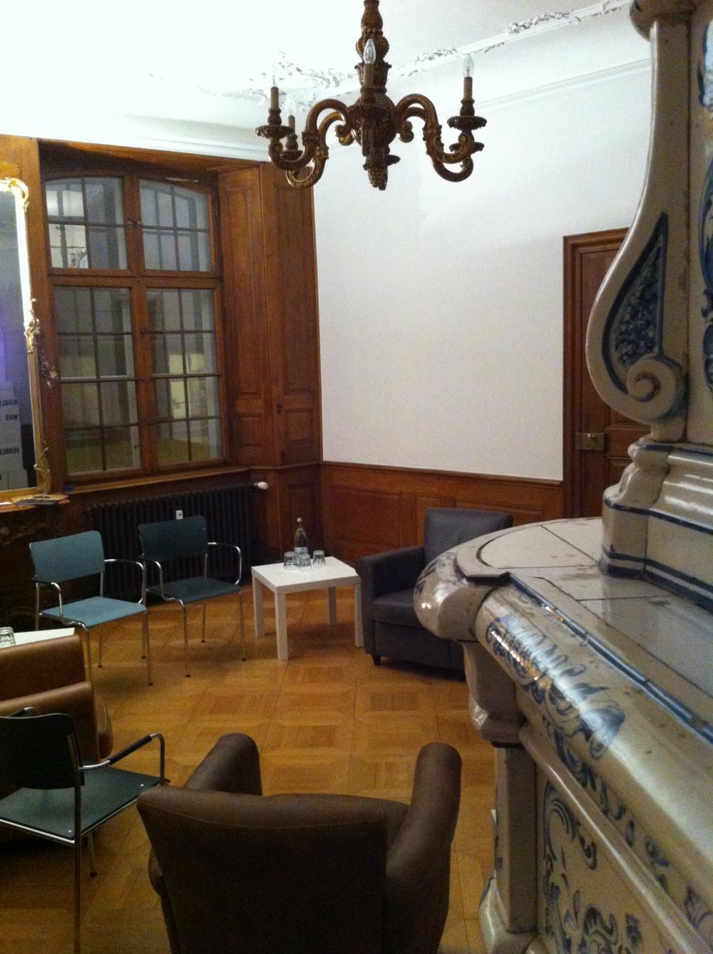 Die Denkpausen finden im Salon vom Ackermannshof statt. Direkt neben dem schönen Porzellanofen.